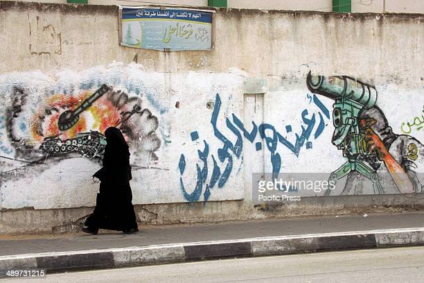 """Palestinian woman walks next to a wall drawing/mural of a militant carrying a rocket in Rafah in the southern Gaza Strip. Nakba, or """"catastrophe"""",..."""