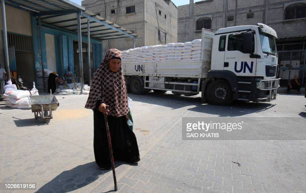 Palestinian woman walks outside an aid distribution center run by the United Nations Relief and Works Agency , in Khan Younis in the southern Gaza...