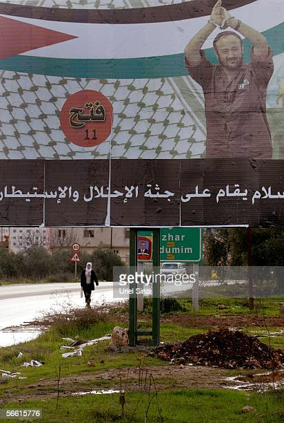A Palestinian woman walks past a campaign poster of jailed Fatah leader Marwan Barghuti January 18 2006 in the West Bank village of Chawara The...