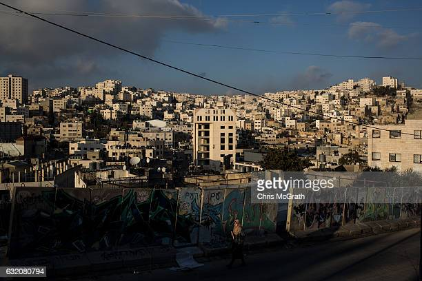 Palestinian woman walks past a concrete barricade on the road that seperates an Israeli settlement and a Palestinian neighbourhood inside the city of...