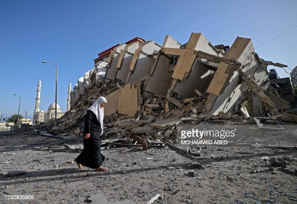 Palestinian woman walks past a destroyed building in Gaza City early on May 12 as Hamas militants and the Israeli army exchanged a barrage of deadly...