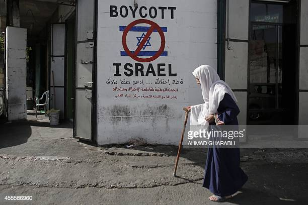 A Palestinian woman walks past a mural calling people to boycott Israeli goods in the alAzzeh refugee camp near the West Bank city of Bethlehem on...