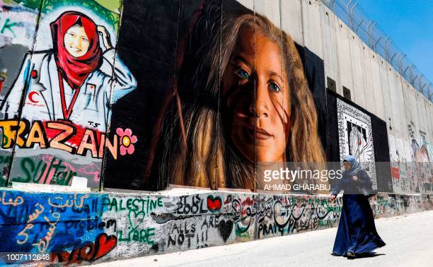 A Palestinian woman walks past a mural painted on Israel's controversial separation barrier in the West Bank city of Bethlehem on July 29 drawn by...