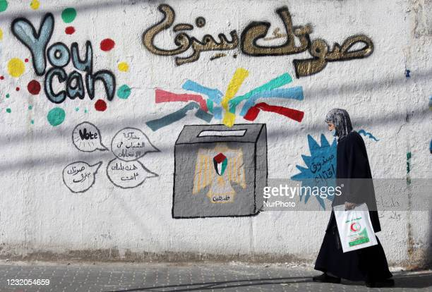 Palestinian woman walks past a mural painting calling on people to vote during the upcoming elections in a street in Gaza City, on April 1, 2021.