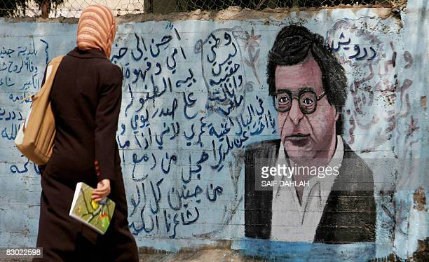A Palestinian woman walks past a street wall decorated with a graffiti of late Palestinian poet Mahmud Darwish�s face in the West Bank city of Jenin...