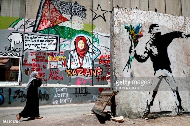 Palestinian woman walks past fresh graffiti painted on Israel's controversial separation barrier in the occupied West Bank city of Bethlehem on June...