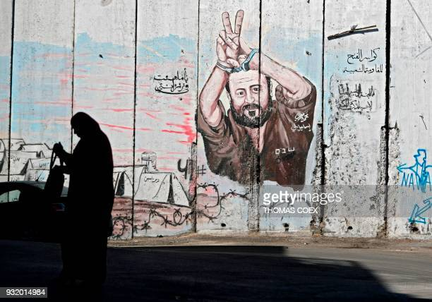 Palestinian woman walks past graffiti depicting Palestinian prisoner Marwan Barghuti on Israel's controversial separation barrier in the West Bank...