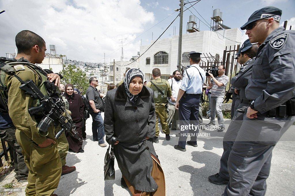 A Palestinian woman walks past Israeli f : Nieuwsfoto's