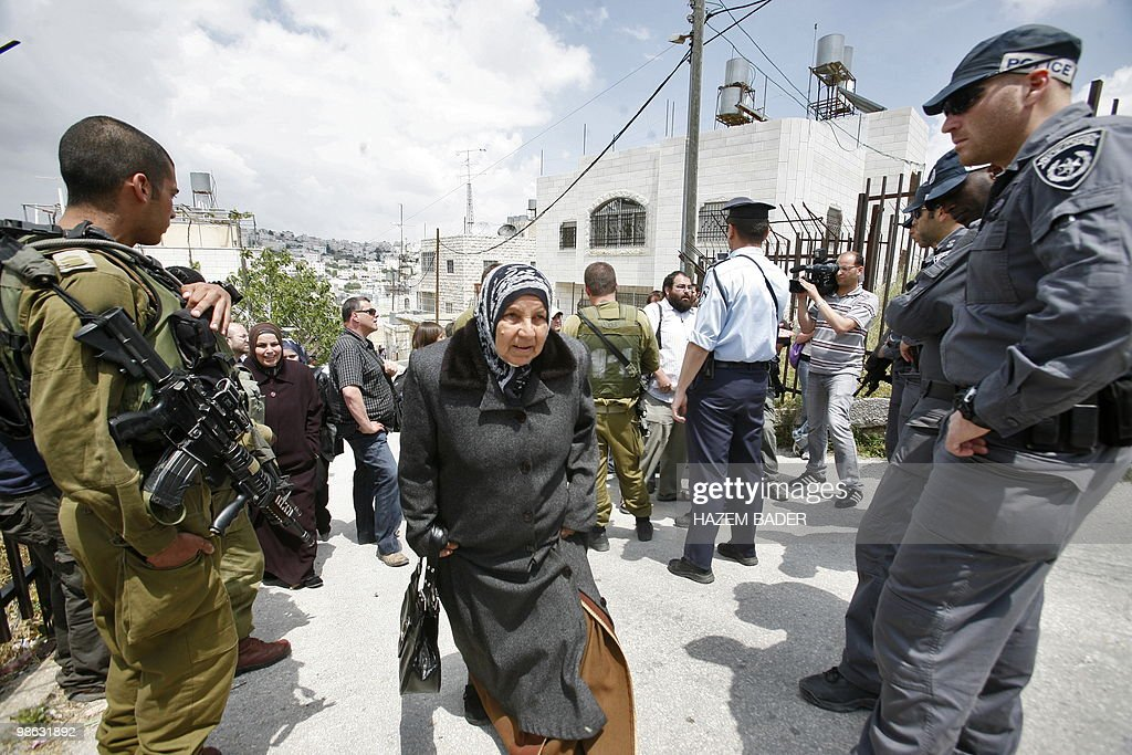 A Palestinian woman walks past Israeli f