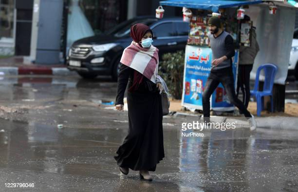 A Palestinian woman walks through a street flooded with rain water during a rainy day in Gaza City on November 26 2020