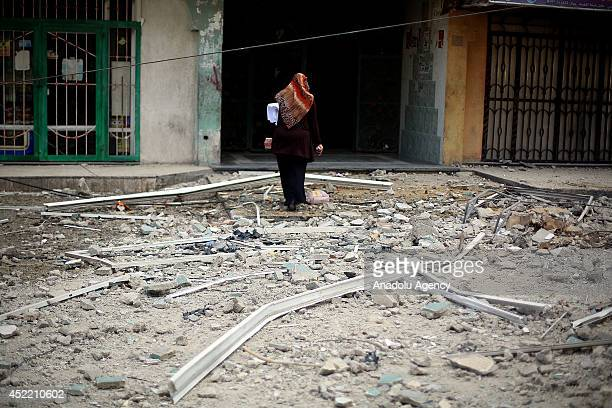 Palestinian woman walks through the ruins after the airstrikes of Israeli army on Gaza City, Gaza on July 16, 2014. Death toll rises to 202 as a...