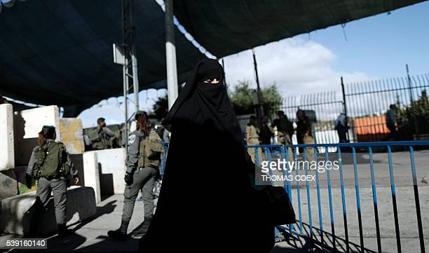 A Palestinian woman walks to the Israeli checkpoint between the West Bank town of Bethlehem and Jerusalem as Palestinians wait to cross to Jerusalem...