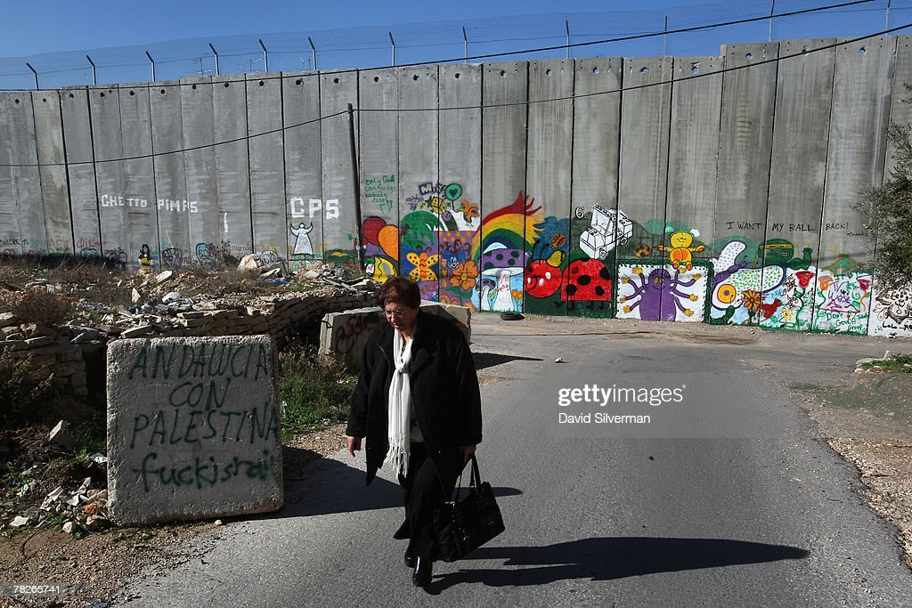 A Palestinian woman walks to work past graffiti on Israel's separation barrier December 5, 2007 on the outskirts of the biblical West Bank city of Bethlehem. Dozens of large-scale artworks by various artists, along with some by elusive British artist Banksy, are part of an exhibition called Santa's Ghetto.
