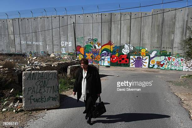 Palestinian woman walks to work past graffiti on Israel's separation barrier December 5 2007 on the outskirts of the biblical West Bank city of...