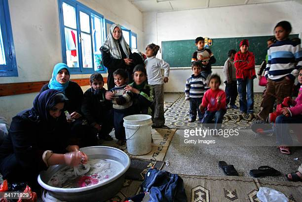 Palestinian woman washes clothes as people take shelter at a United Nations aid centre situated in a school on January 5 2009 in Rafah southern Gaza...