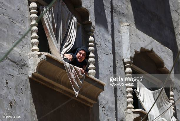 Palestinian woman watches the funeral procession of Hamas military chief Bassem Issa, killed a day earlier in an Israeli air stike, in Gaza City, on...