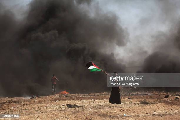 Palestinian woman waves a Palestine flag to encourage others as mass demonstrations continue on May 14 2018 in Gaza City Gaza Israeli soldiers killed...