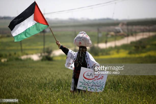 Palestinian woman waves her national flag during an event marking Land Day near the IsraelGaza border as mass rallies planned to commemorate the...