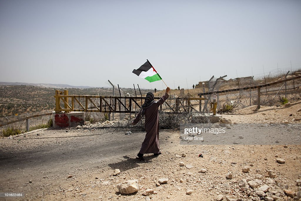 A Palestinian woman waves the Palestinian national flag near an Israeli barrier, against Israel's attack on the flotilla earlier this week, on June 4, 2010 in Bil'lan, the West Bank. Israel has faced international criticism over the deadly raid on May 31, aboard a ship carrying humanitarian aid to the Gaza Strip.