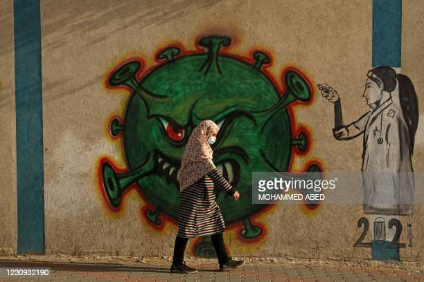 Palestinian woman, wearing a protective mask amid the COVID-19 pandemic, walks past a coronavirus-inspired mural in Gaza City, on February 2, 2021.