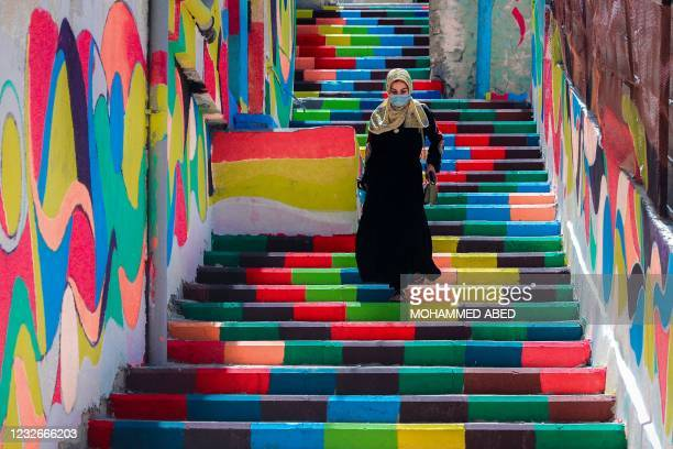 Palestinian woman, wearing a protective mask amid the COVID-19 pandemic, walks down steps decorated with vibrant colours in the al-Daraj...