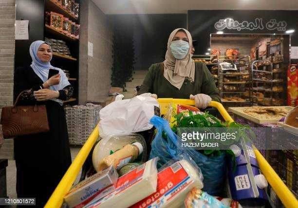 A Palestinian woman wearing protective masks due to the COVID19 coronavirus pandemic pushes her cart loaded with groceries and goods as she shops at...