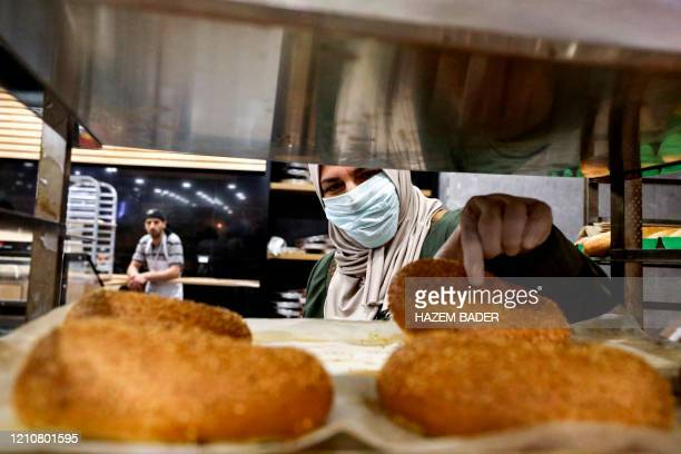 A Palestinian woman wearing protective masks due to the COVID19 coronavirus pandemic picks out freshlybaked pastries from a tray as she shops for...
