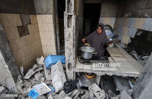 Palestinian woman who has returned to her neighbourhood, cooks a meal in what remains of her home, hit by Israeli bombardment in Gaza City, after a...