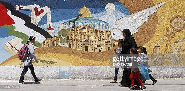 A Palestinian woman with children walks past a mural showing the city of Jerusalem and the cartoon characture known as Handala holding a key as...