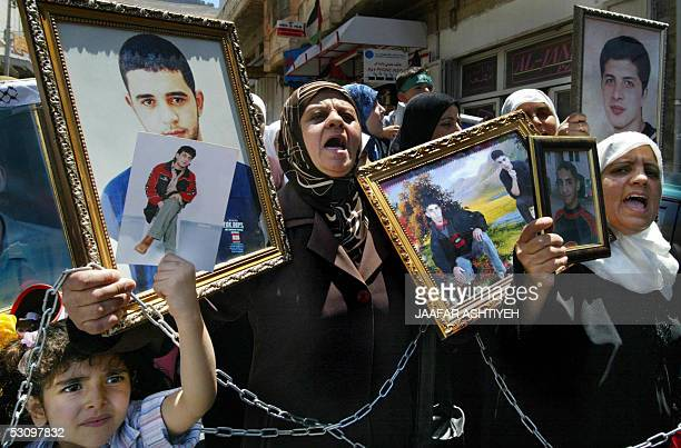Palestinian women and children hold up chains and pictures of relatives held in Israeli jails during a protest 18 June 2005 in the northern West Bank...