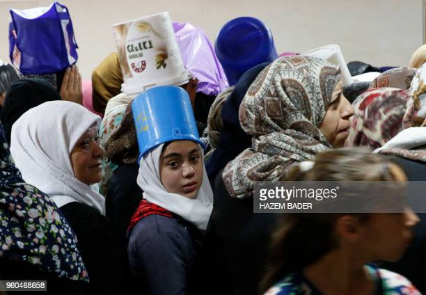 Palestinian women and children queue up at a charity kitchen run by the Islamic Waqf in the West Bank town of Hebron to receive free food on May 20...