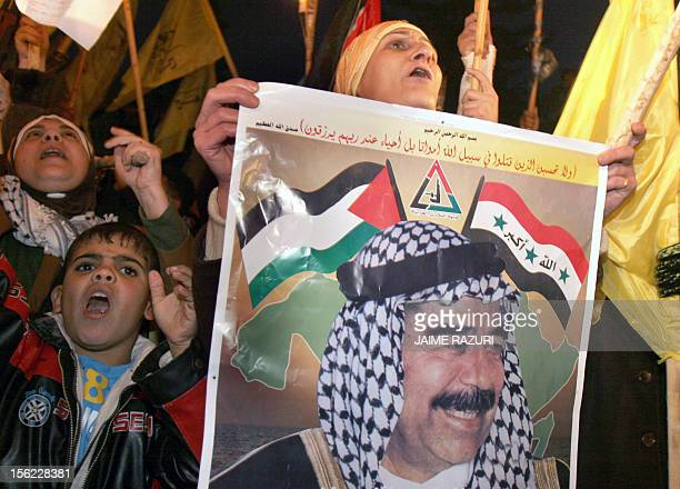 Palestinian women and children supporters of Fatah hold a poster of former Iraqi leader Saddam Hussein during a rally in Gaza City 31 December 2006...