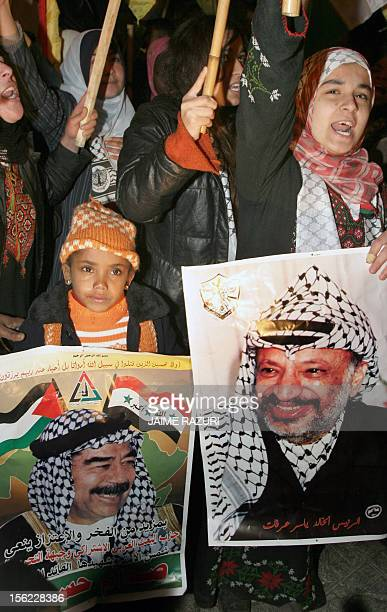 Palestinian women and children supporters of Fatah hold a poster of former Iraqi leader Saddam Hussein and late Palestinian leader Yasser Arafat...