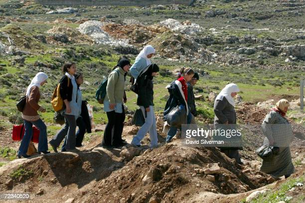 Palestinian women and schoolgirls bypass an Israeli army roadblock February 20, 2002 in the outskirts of the West Bank town of Ramallah. Israeli...