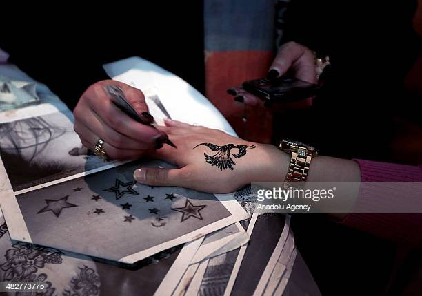 Palestinian women apply henna to their hands at Rashad alShawa Cultural Center within the 'Mother and Child' activity on April 3 2014 in Gaza City...