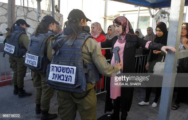 Palestinian women are checked at an Israeli checkpoint between the West Bank town of Bethlehem and Jerusalem as they head to the first Friday prayers...