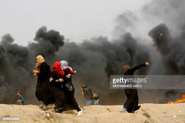 Palestinian women attend throw stones past smoke plume rusing from burning tires during clashes with Israeli forces across the border following a...