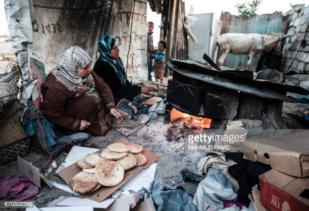 Palestinian women bake bread next to their makeshift home in the Khan Yunis refugee camp in the southern Gaza Strip on April 19 2017 The Gaza Strip's...