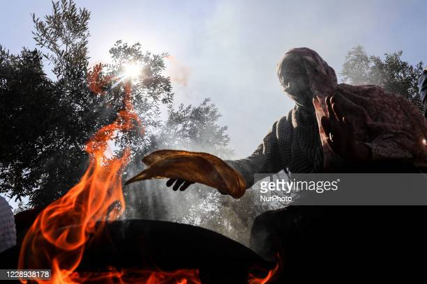 Palestinian women bake bread on firewood in an olive grove during the yearly harvest in Khan Yunis, in the southern Gaza Strip, on October 7, 2020.