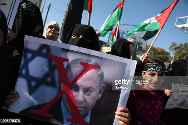 Palestinian women burn posters of US President Donald Trump's and Israeli President Benjamin Netanyahu during a protest after the White House froze...