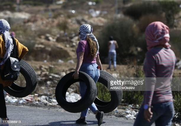 TOPSHOT Palestinian women carry tires during clashes with Israeli troops at a protest in solidarity with Palestinian prisoners held in Israeli jails...