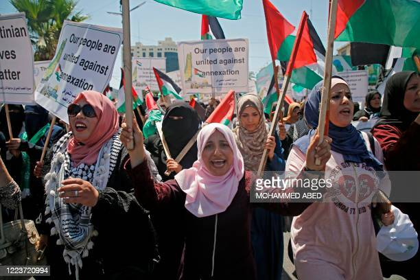 Palestinian women chant and lift placards and national flags during a demonstration against Israel's West Bank annexation plans in Gaza City on July...