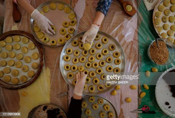 Palestinian women, clad in gloves due to the COVID-19 coronavirus pandemic, prepare traditional biscuits ahead of the upcoming Muslim holiday of Eid...