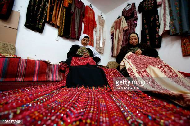 TOPSHOT Palestinian women cross stich traditional Palestinian dresses known as 'Thobe' in Idna village near the West Bank town of Hebron on Januray 8...