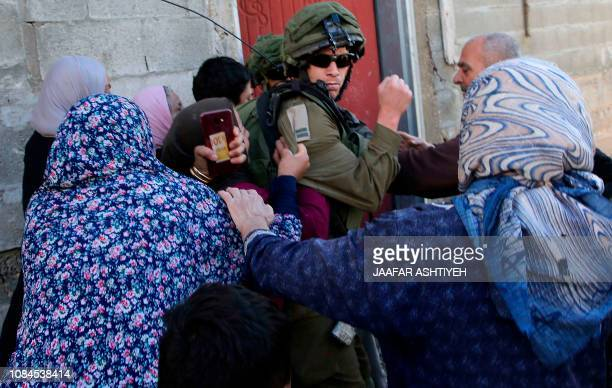 TOPSHOT Palestinian women from the village of Kfar Qaddum near Nablus in the occupied West Bank scuffle with an Israeli soldier as they try to...