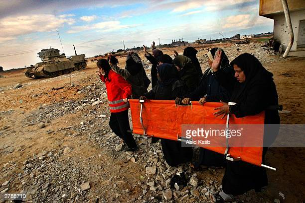 Palestinian women hold a stretcher as they approach the body of Palestinian teenager, Jihad Mousa Al-Akhras December 6, 2003 in the Rafah Refugee...