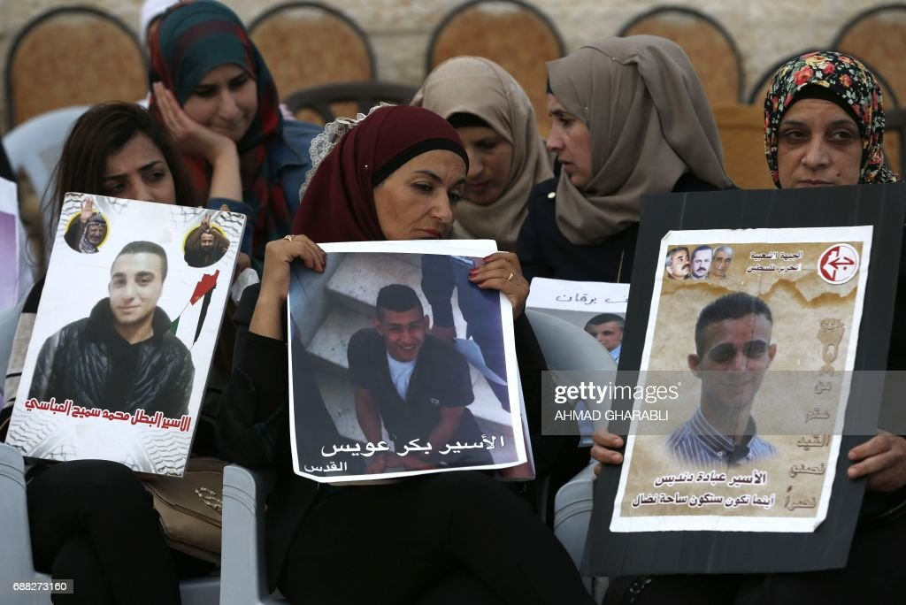 TOPSHOT - Palestinian women hold portraits of relatives imprisoned in Israeli jails during a protest in front of the Red Cross offices in east Jerusalem on May 25, 2017, as hundreds of the detainees entered the second month of a hunger strike. Palestinian president Mahmud Abbas said he has asked the United States to mediate on a standoff between Israeli authorities and Palestinian prisoners on a weeks-long hunger strike. /