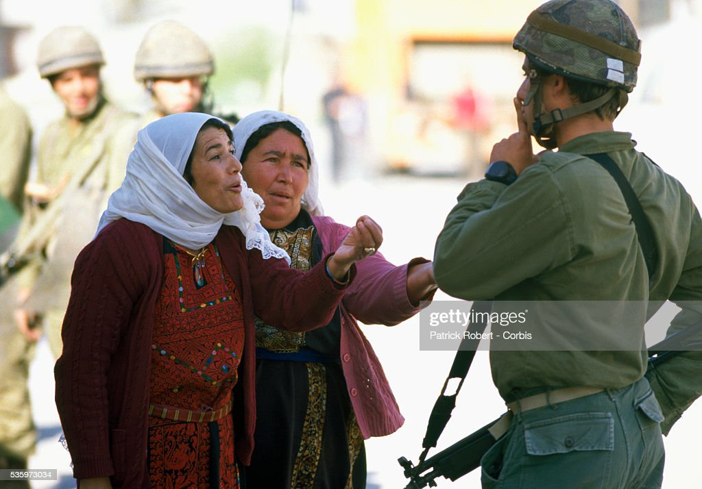 Palestinian women implore Israeli soldiers to release arrested students from their custody.