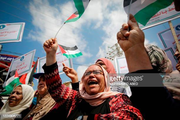 Palestinian women lift national flags and placards during a rally for supporters of the Fateh movement against Israel's West Bank annexation plans,...