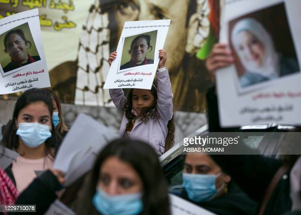 Palestinian women lift placards and banners during a rally in support of 41 women detained in Israeli prisons in the city center of Ramallah in the...